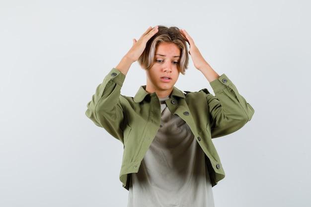 Mooie tienerjongen die de handen op het hoofd houdt in een groen jasje en er verontrust uitziet. vooraanzicht.
