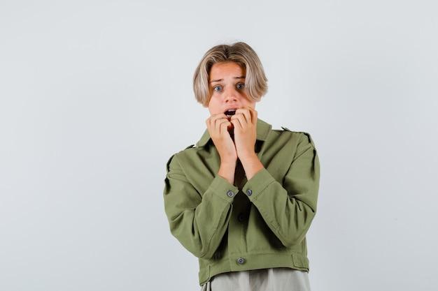 Mooie tienerjongen die handen in de buurt van open mond houdt in een groen jasje en er doodsbang uitziet. vooraanzicht.