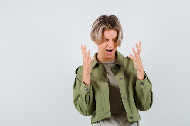 Mooie tienerjongen die handen op een agressieve manier opheft terwijl hij in een groen jasje schreeuwt en gefrustreerd kijkt, vooraanzicht.