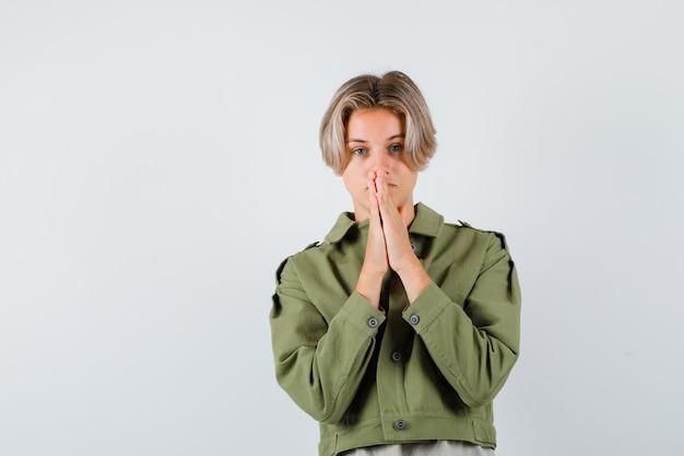 Mooie tienerjongen die handen vasthoudt in een biddend gebaar in een groen jasje en er hoopvol uitziet, vooraanzicht.