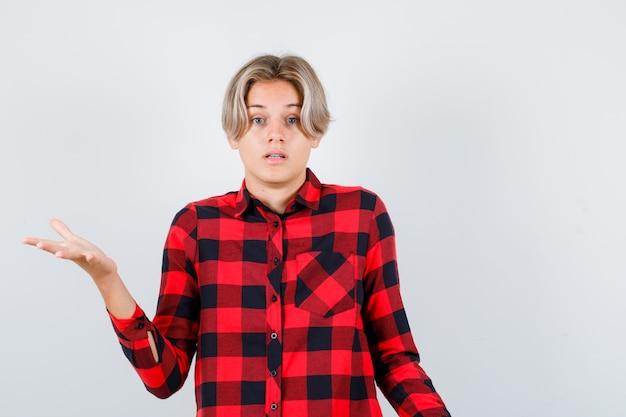 Mooie tienerjongen die hulpeloos gebaar toont in geruit overhemd en er geen idee van heeft. vooraanzicht.