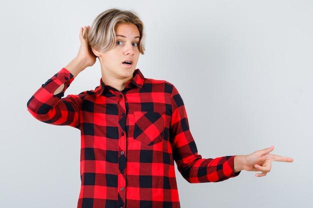 Mooie tienerjongen die naar rechts wijst, met de hand achter het oor in een geruit overhemd en er verbaasd uitziet, vooraanzicht.