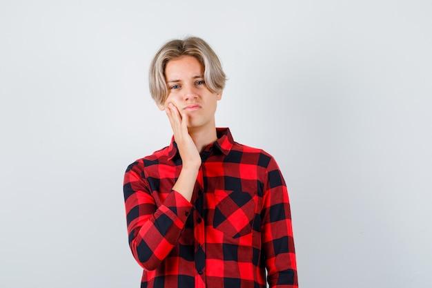 Mooie tienerjongen die op zijn wang leunt in een geruit overhemd en er ontevreden uitziet, vooraanzicht.