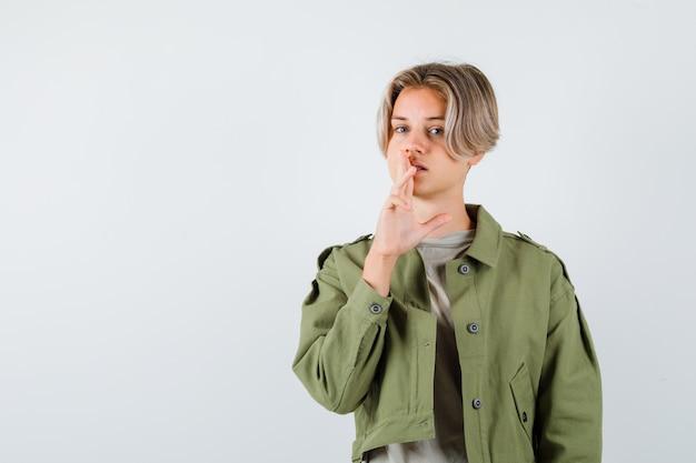 Mooie tienerjongen die stiltegebaar in groene jas toont en er verstandig uitziet