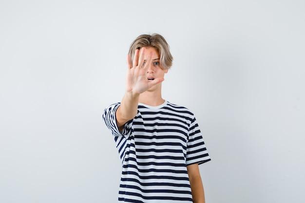 Mooie tienerjongen die stopgebaar toont in gestreept t-shirt en er nerveus uitziet, vooraanzicht.