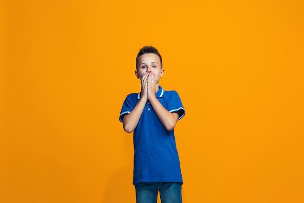 Mooie tienerjongen die verrast kijkt die op sinaasappel wordt geïsoleerd