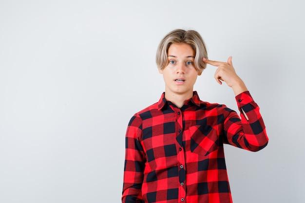 Mooie tienerjongen die zelfmoordgebaar in geruit overhemd toont en verbaasd kijkt. vooraanzicht.