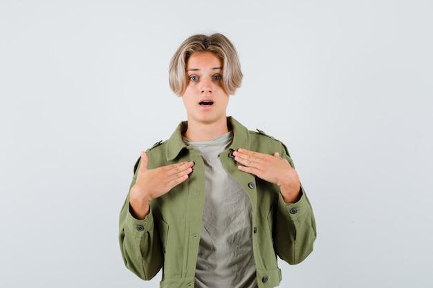 Mooie tienerjongen die zijn handen op de borst houdt in een groen jasje en er geschokt uitziet. vooraanzicht.