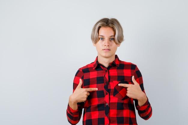 Mooie tienerjongen in geruit hemd die naar zichzelf wijst en verbaasd kijkt, vooraanzicht.