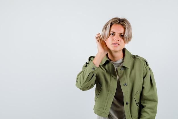 Mooie tienerjongen in groen jasje die hand achter het oor houdt en verbijsterd kijkt