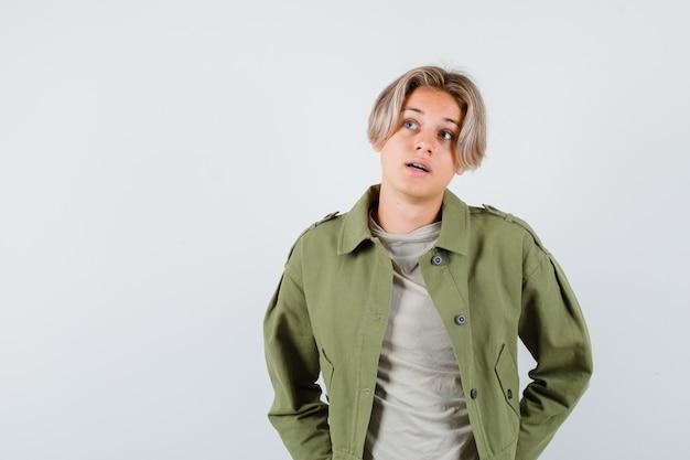 Mooie tienerjongen in groen jasje die omhoog kijkt en nadenkend, vooraanzicht kijkt.