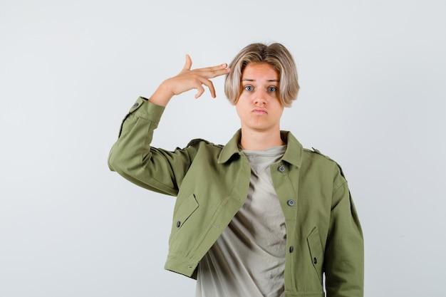Mooie tienerjongen in groen jasje die zelfmoordgebaar toont en neergeslagen kijkt