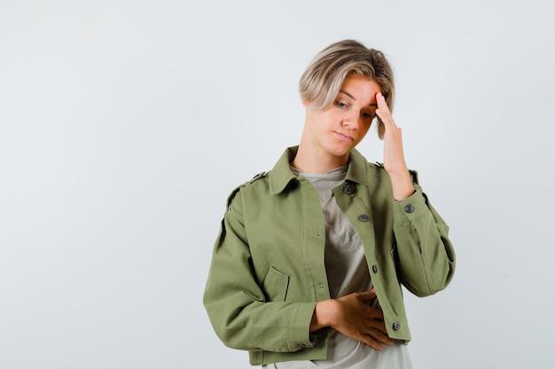 Mooie tienerjongen in groene jas die met het hoofd op de hand leunt en er verdrietig uitziet, vooraanzicht.