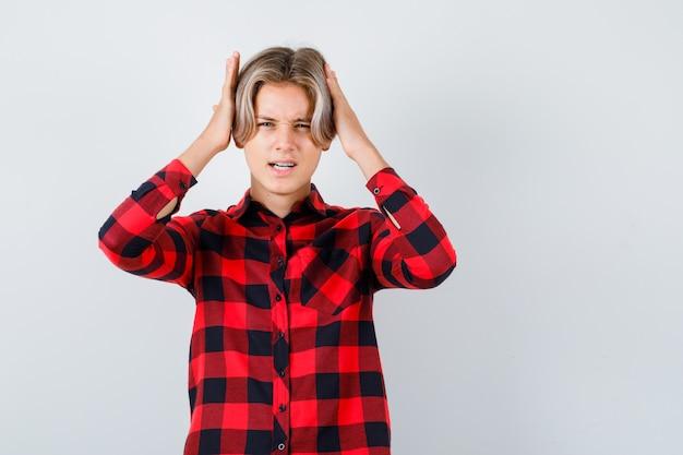 Mooie tienerjongen met de handen op het hoofd in een geruit overhemd en er geïrriteerd uitzien. vooraanzicht.