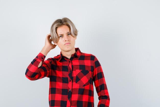 Mooie tienerjongen met hand achter het oor, afluistert geheim in geruit overhemd en kijkt verward, vooraanzicht.