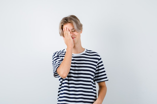 Mooie tienerjongen met hand op gezicht in gestreept t-shirt en peinzend, vooraanzicht.