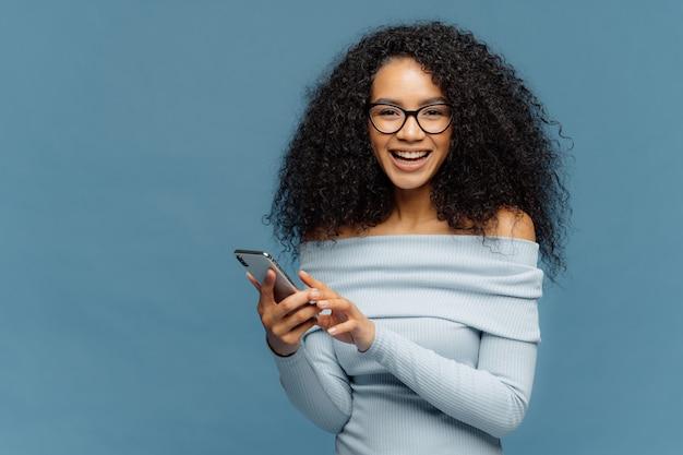 Mooie tienermeisje geniet van online communicatie, houdt moderne mobiele telefoon, controleert e-mail box