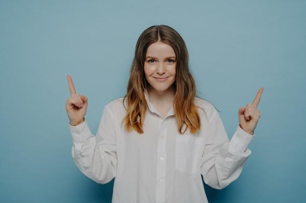 Mooie tienermeisje in wit overhemd met zelfvoldane glimlach en tevreden emotie op gezicht omhoog wijzend met haar vingers, die aangeeft op kopieerruimte, geïsoleerd op blauwe achtergrond. verkoop- en promotieconcept