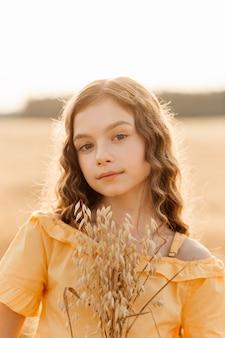 Mooie tienermeisje met lang haar wandelen door een tarweveld op een zonnige dag. buiten portret. schoolmeisje ontspannen