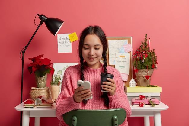 Mooie tienermeisje met twee vlechten houdt mobiele telefoon, houdt wegwerp kopje drank