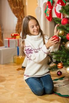 Mooie tienermeisje poseren bij de kerstboom met rode kerstbal