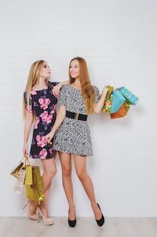 Mooie tienermeisjes die boodschappentassen dragen