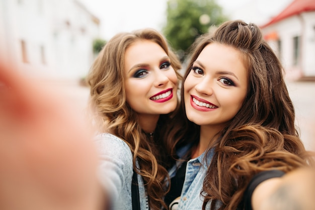 Mooie tienermeisjes die met kapsels en rode lippen bij camera glimlachen.