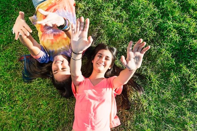 Mooie tienermeisjes die plezier hebben in het zomerpark. buitenshuis