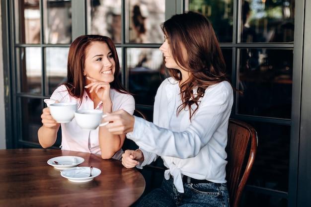 Mooie tieners die pret hebben en toost met koffiekoppen maken in koffie