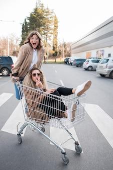 Mooie tieners poseren met winkelwagen