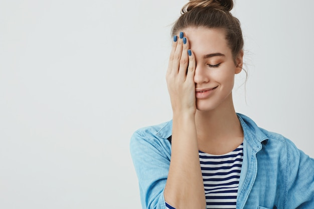Mooie tienervrouw die één oog behandelt met haar hand