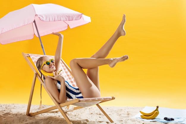 Mooie tienervrouw met het mooie kapsel ontspannen op strandstoel