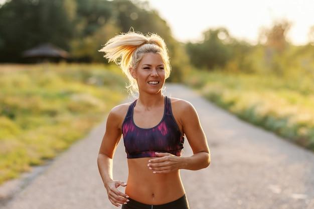 Mooie toegewijde blonde vrouw met paardenstaart en in sportkleding uitgevoerd in de natuur op zonnige zomerdag. van je middel omhoog.