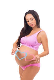Mooie toekomstige moeder wachtende baby. jongen, meisje tweeling. blauwe en roze hartjes bij de zwangere buik.
