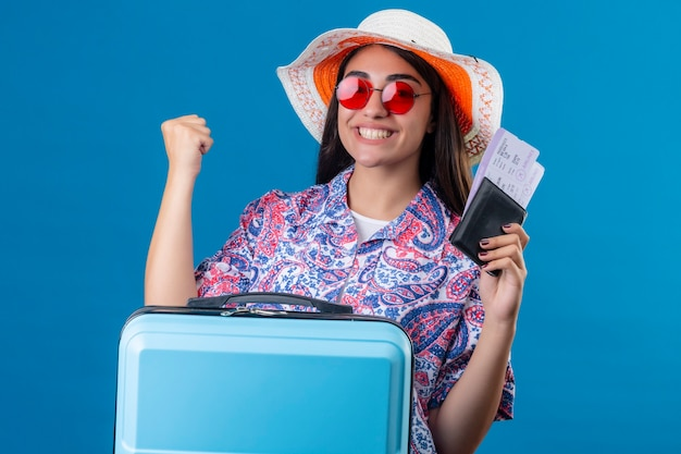 Mooie toeristische vrouw in zomerhoed dragen rode zonnebril houden reiskoffer en paspoort met kaartjes met glimlach op gezicht blij en positief vuist verhogen na een victo