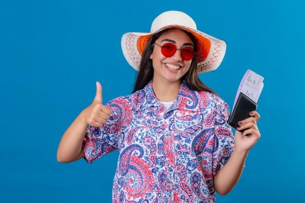 Mooie toeristische vrouw in zomerhoed met rode zonnebril met paspoort en kaartjes glimlachend vrolijk weergegeven: duimen klaar voor vakantie over geïsoleerde blauwe ruimte