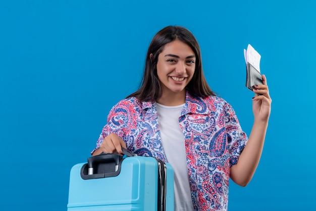 Mooie toeristische vrouw met reiskoffer en paspoort met kaartjes met glimlach op gezicht gelukkig en positief reisconcept staande over blauwe ruimte