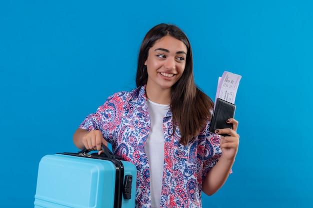 Mooie toeristische vrouw met reiskoffer en paspoort met kaartjes opzij kijken met glimlach op gezicht gelukkig en positief reisconcept staande over blauwe ruimte