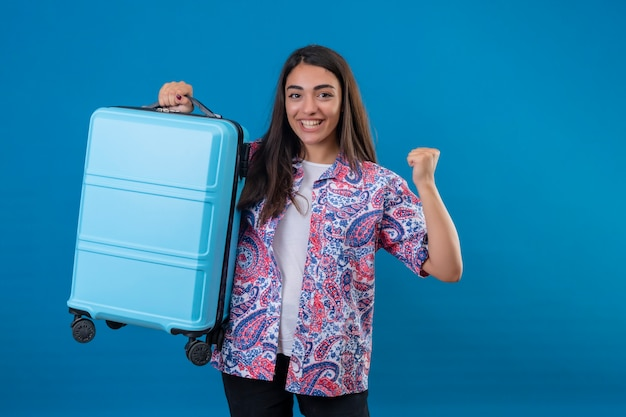 Mooie toeristische vrouw met reiskoffer kijkt opgewonden verheugd over haar succes en overwinning haar vuisten balancerend met vreugde blij om haar doel en doelen te bereiken staande over geïsoleerde blauwe achtergrond