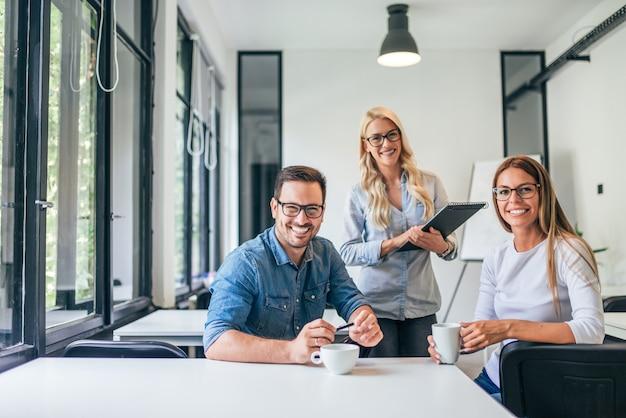 Mooie toevallige bedrijfsmensen in modern helder bureau. kijkend naar de camera. teamwork concept.