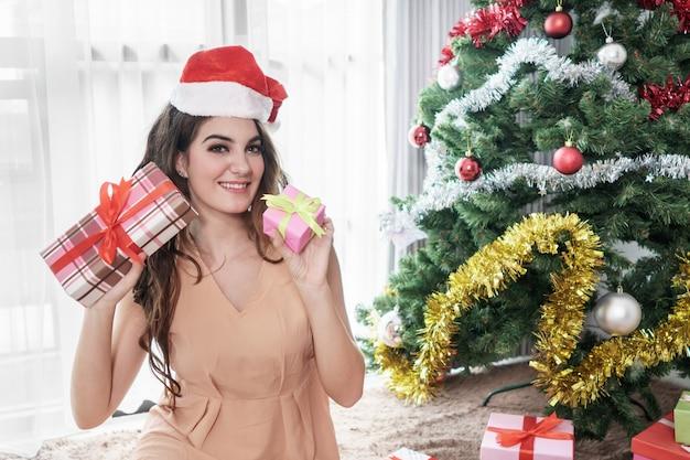 Mooie toevallige vrouw die de hoedenzitting dragen van santa terwijl het houden