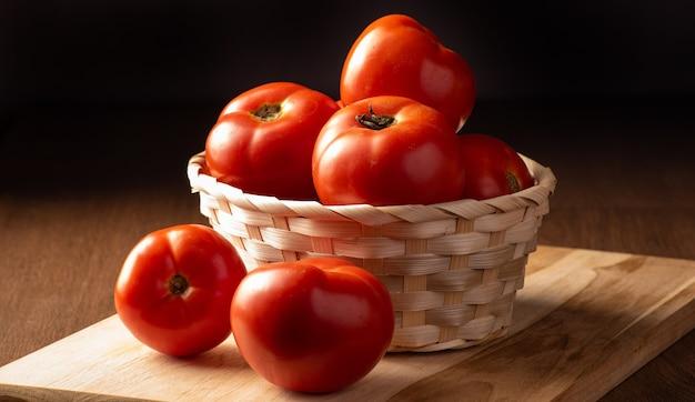 Mooie tomaten gerangschikt in een mand en op houten donkere achtergrond