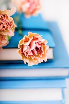 Mooie toppen van de anjerbloemen van de zalmkleur op stapel blauwe boeken