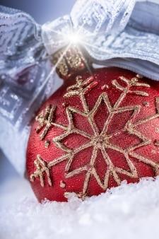 Mooie traditionele kerstbal gelegd in de sneeuw met mooi lint en glanzende glinstering.