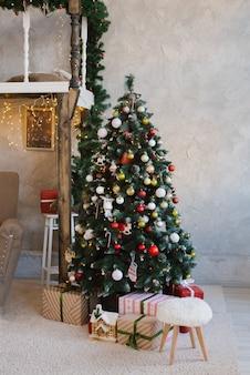Mooie traditionele rode kerstboom in het interieur van de woonkamer van het huis