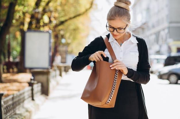 Mooie trendy blonde bedrijfsvrouw die op de smartphone spreekt en iets in een handtas zoekt.