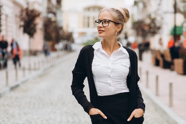 Mooie trendy blonde zakenvrouw in glazen met map met documenten in haar handen buitenshuis.