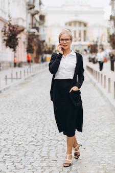 Mooie trendy blonde zakenvrouw in glazen met smartphone en handtas van documenten in haar handen buitenshuis.