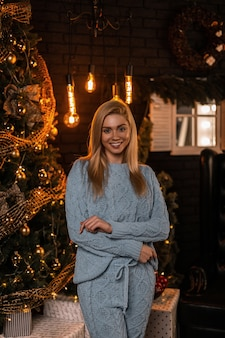Mooie trendy jonge vrouw in een stijlvol gebreid pak staat en lacht lief in de woonkamer met een kerstboom met slingers met verlichting en geschenken