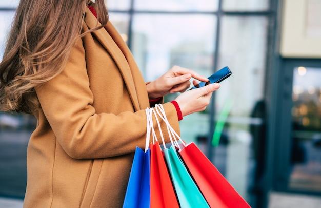 Mooie trendy jonge vrouw met veel kleurrijke boodschappentassen in goed humeur met slimme telefoon en creditcard tijdens het wandelen in het winkelcentrum tijdens zwarte vrijdag